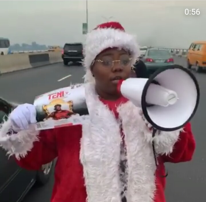 Teni Rocks Father Christmas Costume, Begs People On The Road To Come To Her Show 1